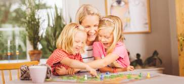Barnflicka i Göteborg spelar spel med barn och skrattar